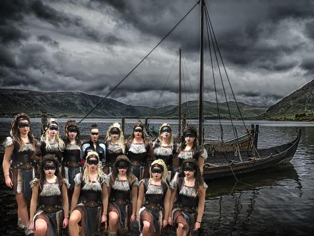 Cometen posieren mit ihrer Trainerin im Wikinger-Kostüm vor einem Boot